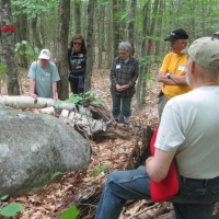 The group studies a glacial rock