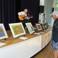 Tom Pirozzoli entertains while guests view the art.  Tom was also a contributing artist.